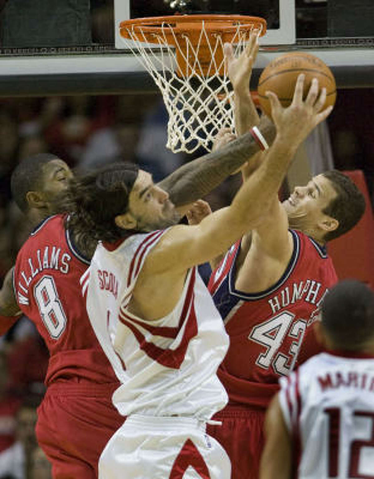 Rockets forward Luis Scola grabs a rebound away from Nets guard Terrence Williams (8) and forward Kris Humphries (43).
