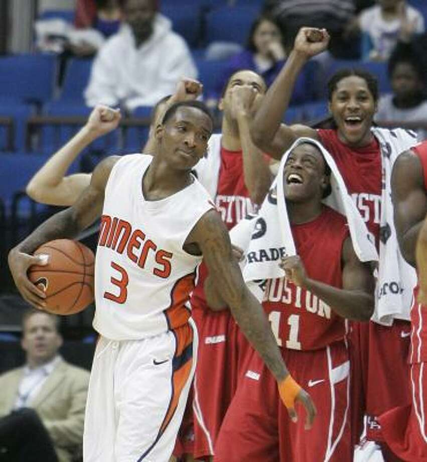 UTEP guard Randy Culpepper holds the ball as the Houston bench cheers at rear, following a whistle in the closing minutes of the Conference USA men's championship NCAA college basketball game in Tulsa, Okla., Saturday, March 13, 2010. Houston won 81-73. Photo: Sue Ogrocki, AP