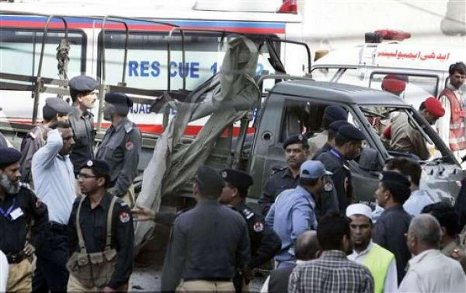 Oficiales de seguridad e investigadores paquistaníes se reúnen cerca de un camión del ejército dañado por un atacante suicida con explosivos, en Lahore, Pakistán, el viernes 12 de marzo del 2010. Photo: K.M.Chaudary, AP