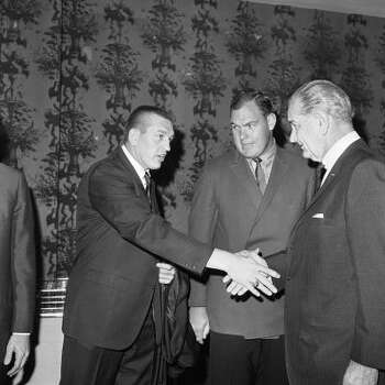 Merlin Olsen, center, watches as Baltimore Colts quarterback Johnny Unitas shakes hands with President Lyndon B. Johnson at the annual Presidential Prayer Breakfast in Washington on Feb. 1, 1968. Photo: John Rous, AP