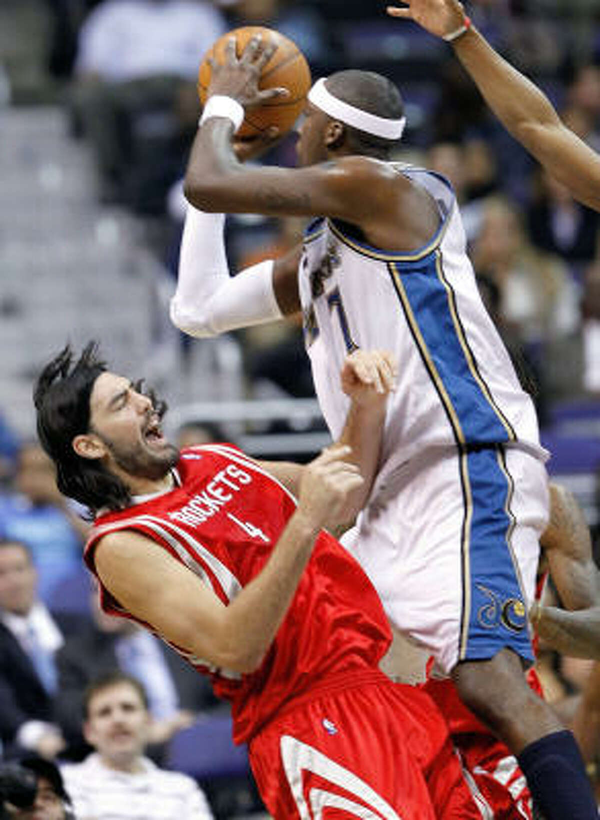 Wizards forward Andray Blatche charges into Rockets forward Luis Scola for a foul.