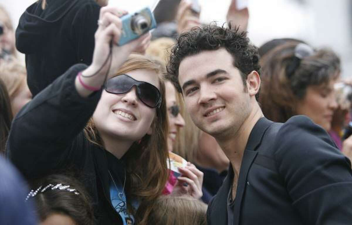 Kevin Jonas takes pictures with a fan.