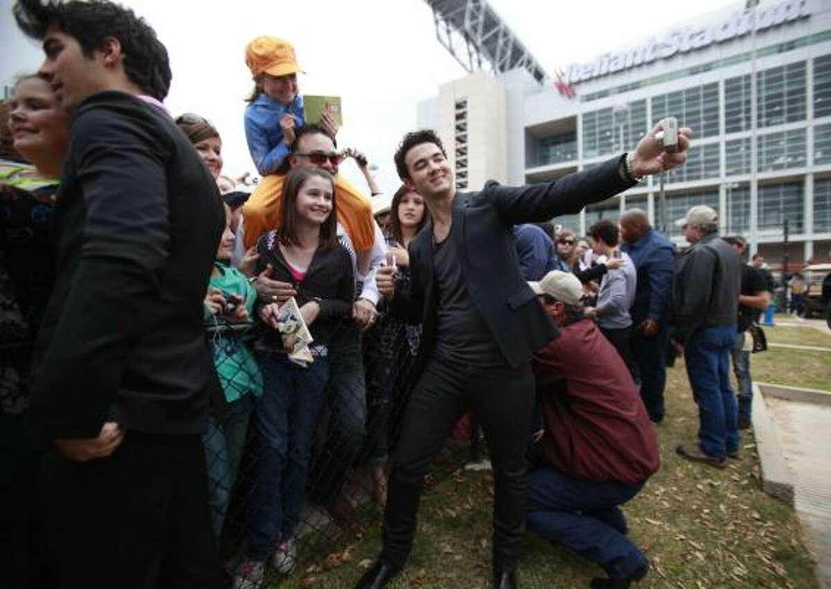 Kevin Jonas snaps a photo with fans.