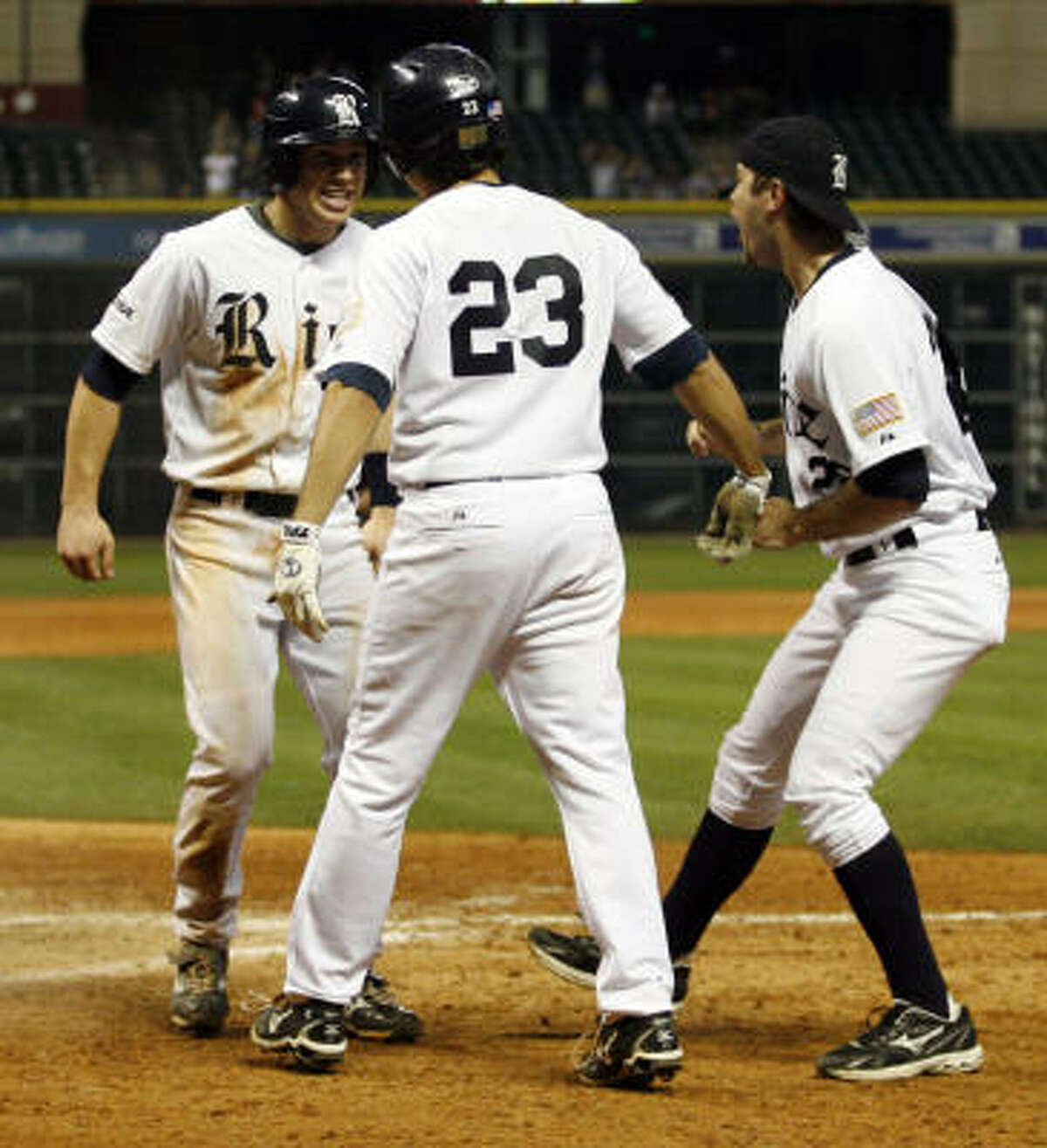 Rice 2B Michael Ratterree, left, is greeted by teammates after scoring the winning run off a hit by DH Chase McDowell (25) in the bottom of the ninth inning defeating TCU on the final night of the Houston College Classic.
