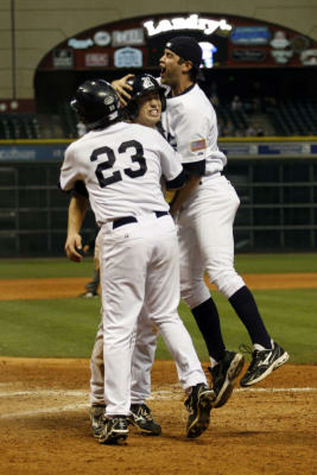 Rice 2B Michael Ratterree (8) is greeted by teammates after scoring the winning run.
