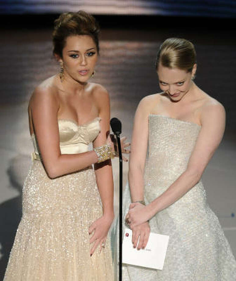 Umm ... so like, ... yeah: Miley Cyrus, left, and Amanda Seyfried stumbled through the presentation of the Best Original Song award. Elocution ladies. Look it up. Photo: Mark J. Terrill, AP