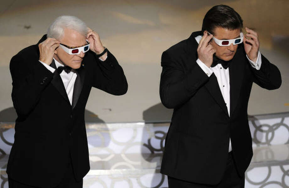 Host Alec Baldwin, right, and Steve Martin check out James Cameron wearing their 3D glasses. Photo: Mark J. Terrill, AP