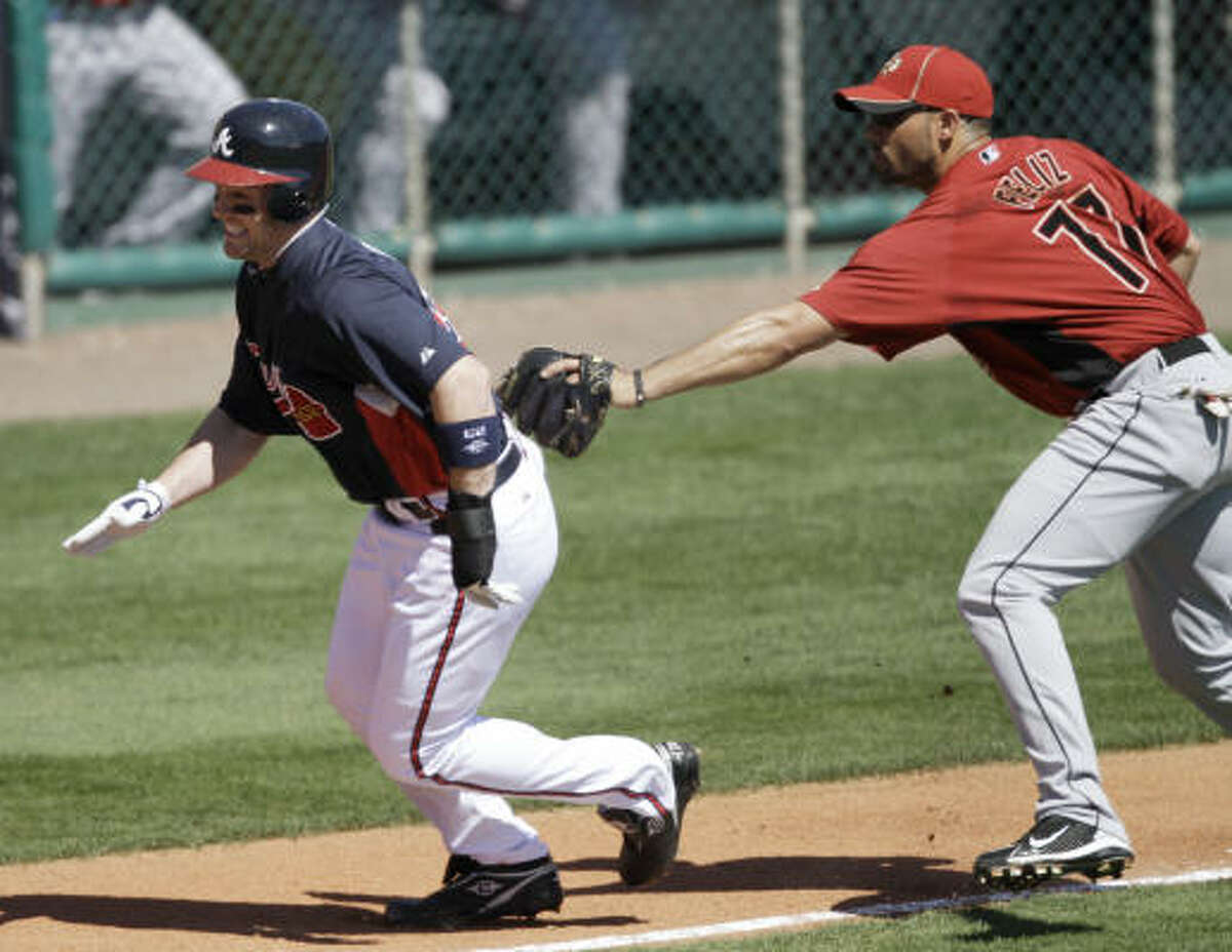 Astros third baseman Pedro Feliz, right, tags out Braves' Matt Diaz on a failed squeeze play from third to home plate.