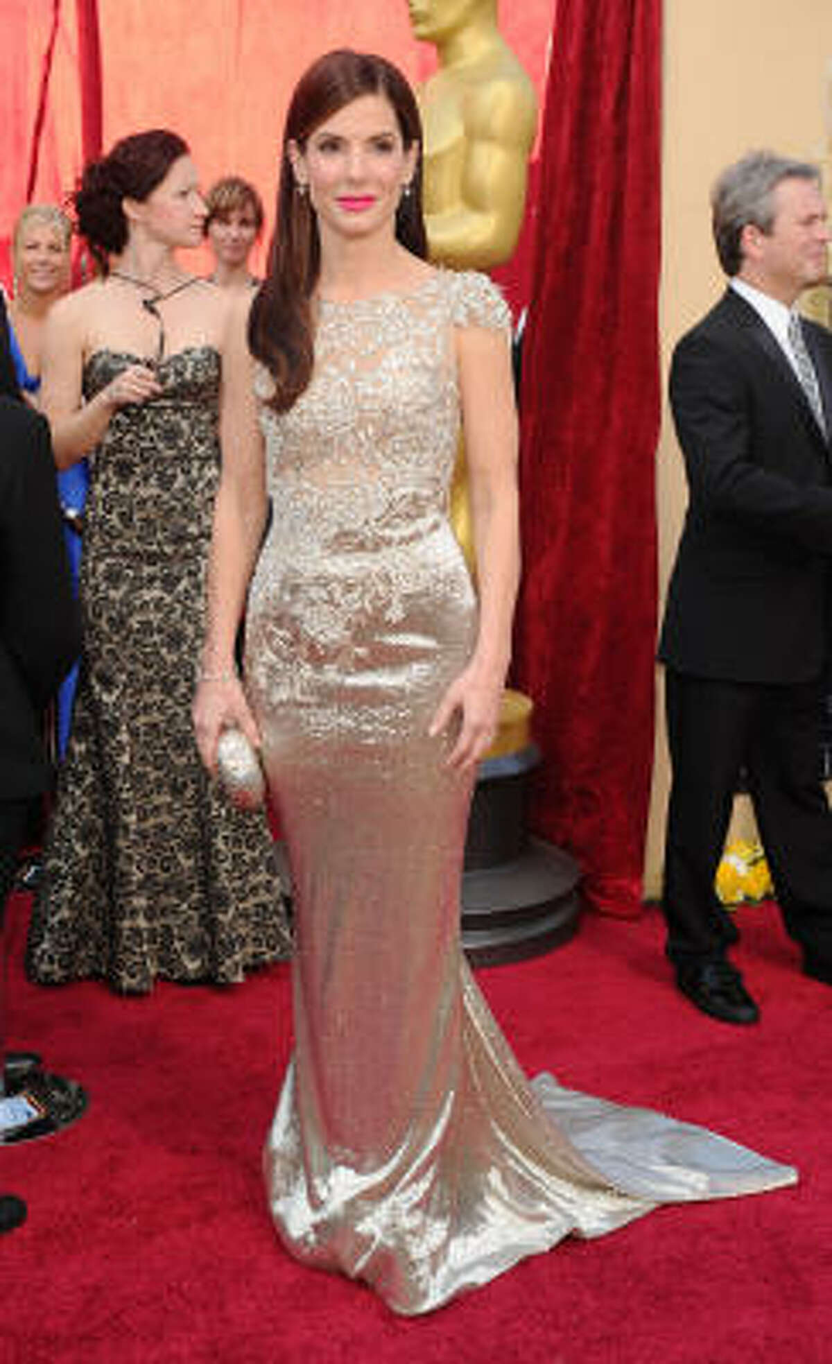 """LIKE OSCAR: Sandra Bullock looks like an Academy Award herself in a beautiful gold gown. """"I don't want these heels to pull this gown down."""""""