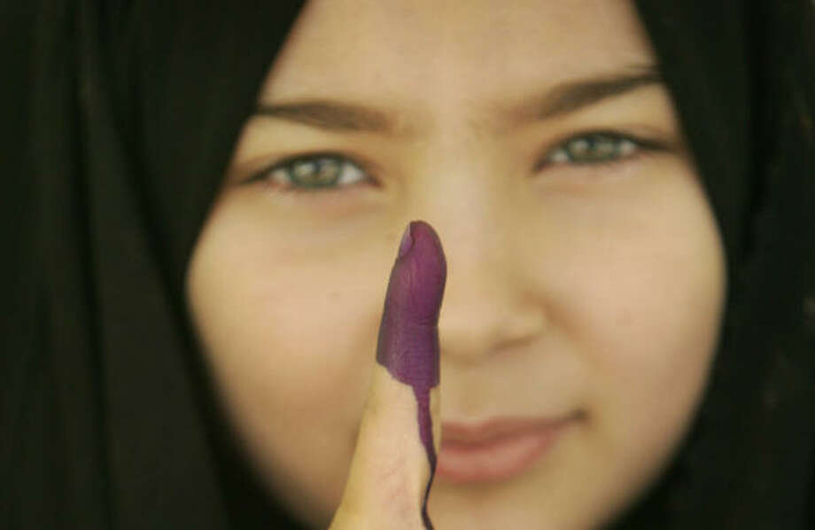 A young Iraqi girl, who accompanied her family to the polling station, asked for her finger to be inked, even though she was too young to vote, shows her inked finger as she leaves the polling station in Karbala, Iraq. Photo: Ahmed Al-Hussainey, AP