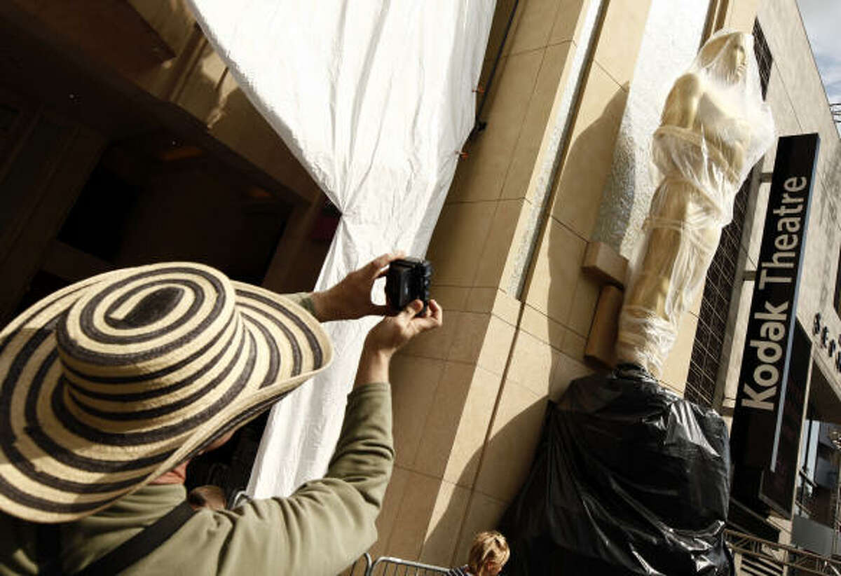 A tourist takes a picture of an Oscar statue in front of the Kodak Theatre in Los Angeles.