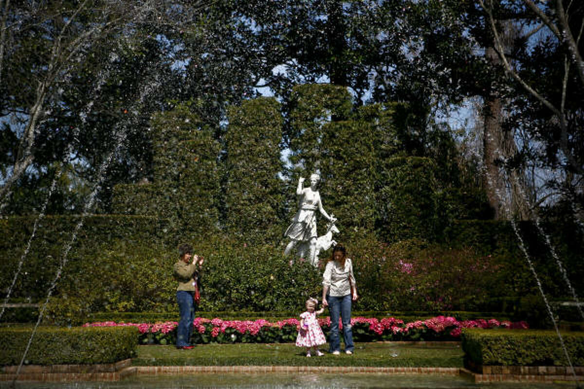 Laura Jones poses for a photo with her daughter Avery (19-months) while Lola Grant looks on while at the Bayou Bend Gardens.