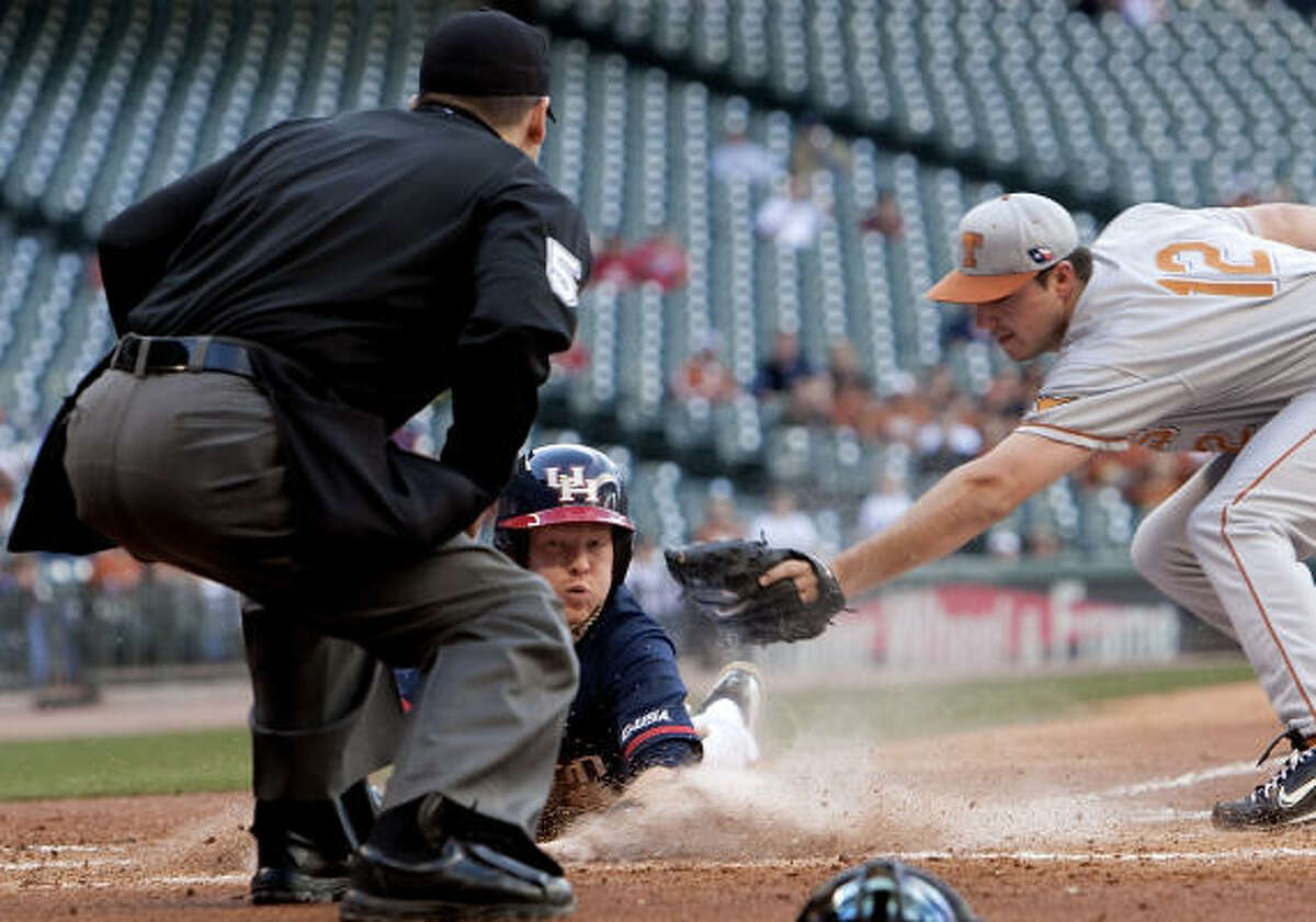 UH's Blake Kelso slides safely into home for the game's only run after a wild pitch from Texas pitcher Brandon Workman, right, in the first inning.