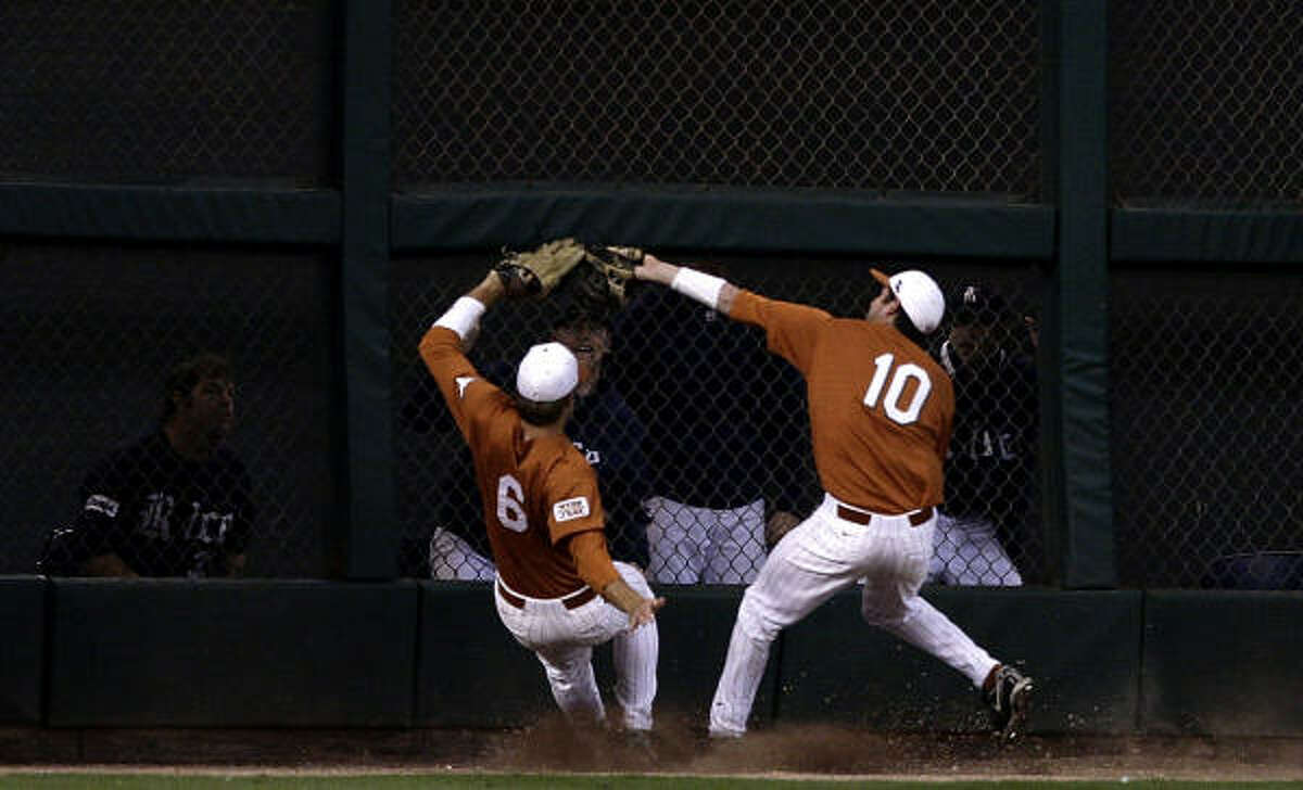 Texas' Connor Rowe, right, makes the catch as he collides with left fielder Kyle Lusson.
