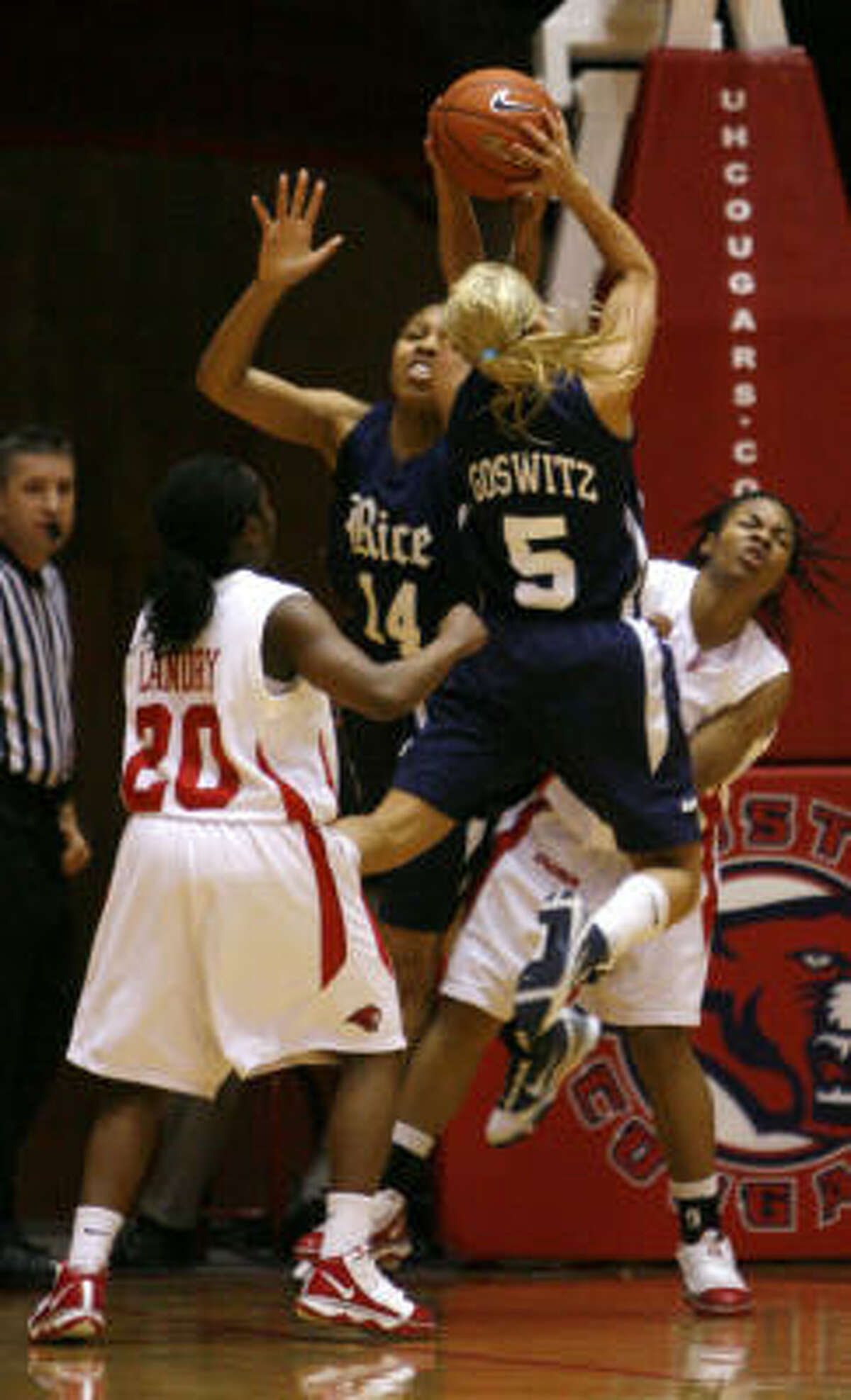 Rice's Jessica Goswitz (5) goes up for the basket over Houston's Brittney Scott, right, as Houston's Porsche Landry (20) watches.