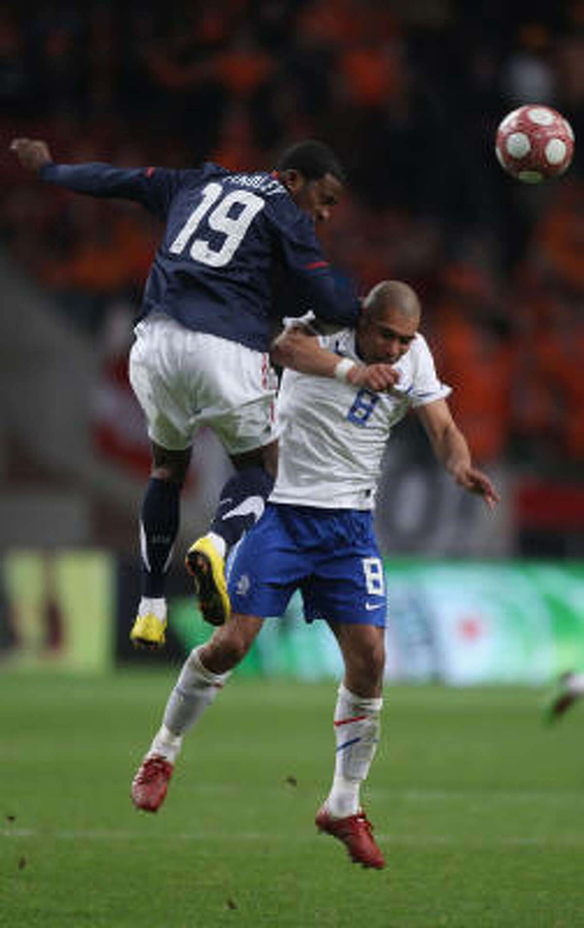 Robert Findley of USA and Nigel de Jong of the Netherlands attack the ball during their matchup.