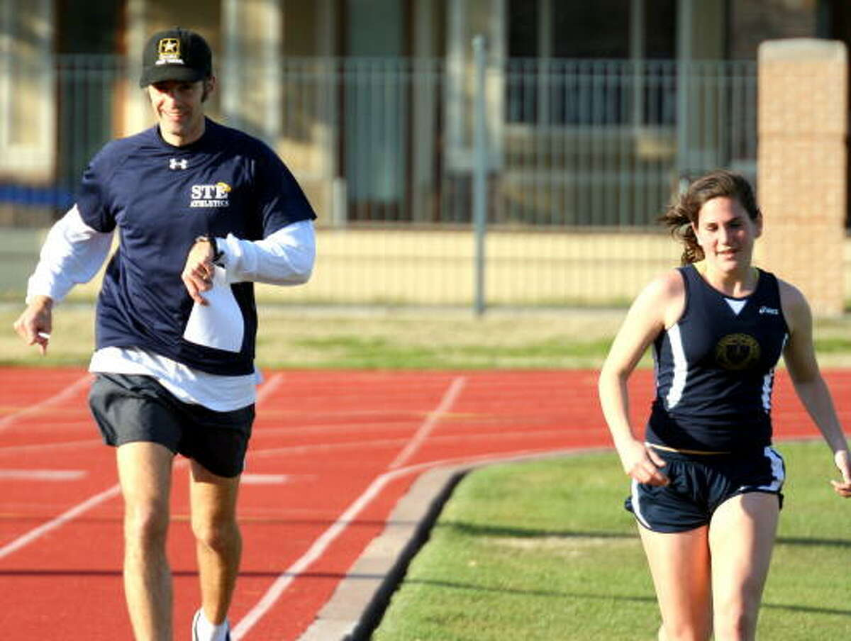 Coach Ramsey of St. Thomas Episcopal runs a cool down lap with his winner of the girls 3200-meter, Claire Coulter.