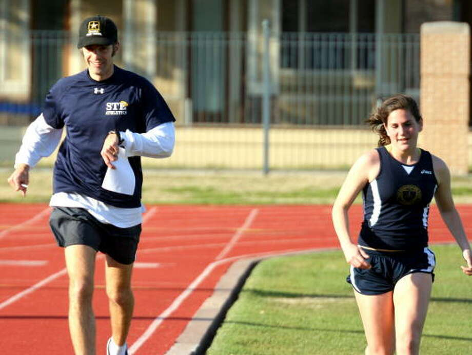 Coach Ramsey of St. Thomas Episcopal runs a cool down lap with his winner of the girls 3200-meter, Claire Coulter. Photo: Gerald James, Chronicle