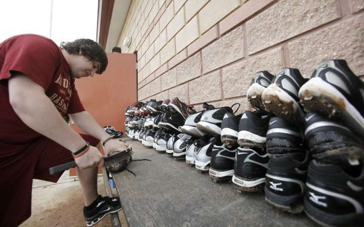Astros clubhouse attendant Ryan Sedivy cleans players' shoes after a spring training workout.