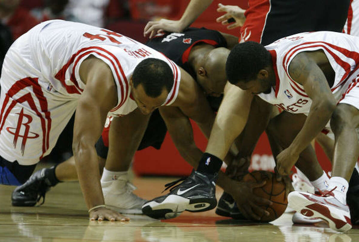 Chuck Hayes, left, and Aaron Brooks, right, go after a loose ball against the Raptors' Jarrett Jack.