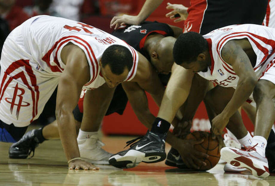 Chuck Hayes, left, and Aaron Brooks, right, go after a loose ball against the Raptors' Jarrett Jack. Photo: Brett Coomer, Chronicle