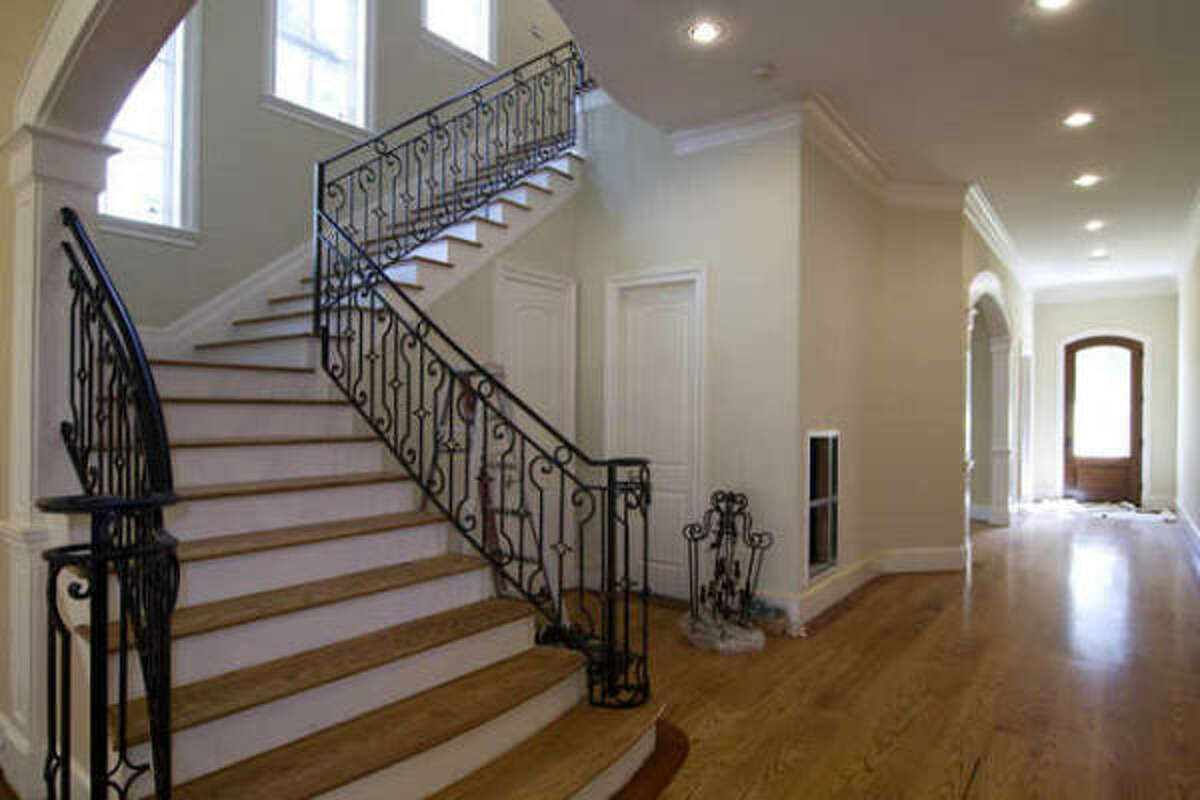 Grand entry hall has a sweeping staircase with custom metalwork. The hallway leads to stately study, gracious formal living & dining rooms & huge family room.