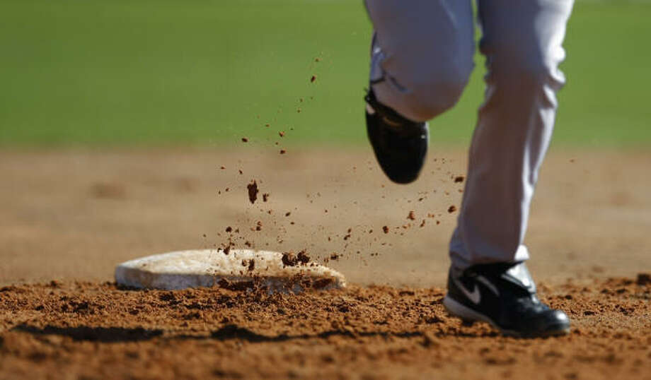 Dirt flies as Astros non-roster invitee catcher Jason Castro circles the bases. Photo: Julio Cortez, Chronicle