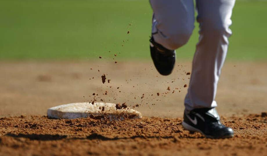 Dirt flies as Astros non-roster invitee catcher Jason Castro circles the bases. Photo: Julio Cortez, Chronicle