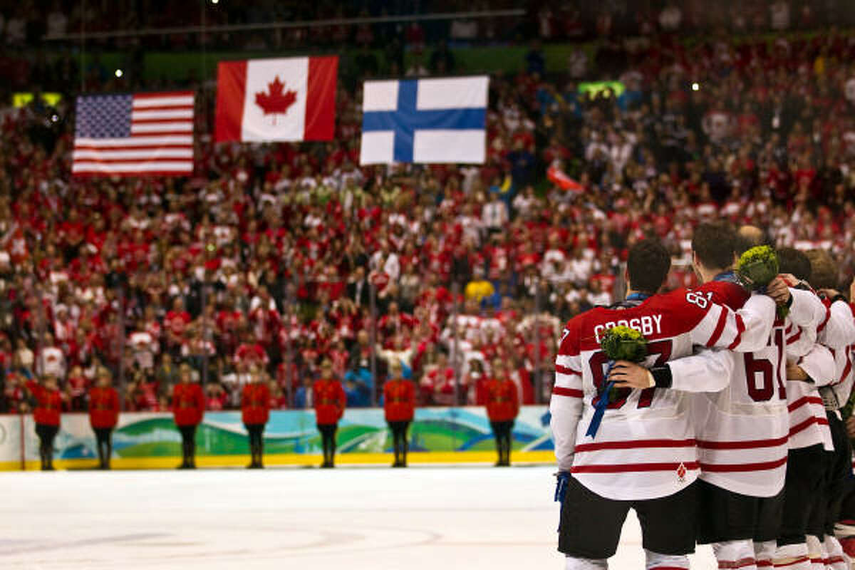 Feb. 28, 2010 | Canada's Sidney Crosby watches as the flags are raised after team Canada received their gold medals after winning the men's ice hockey gold medal game at the 2010 Winter Olympics.