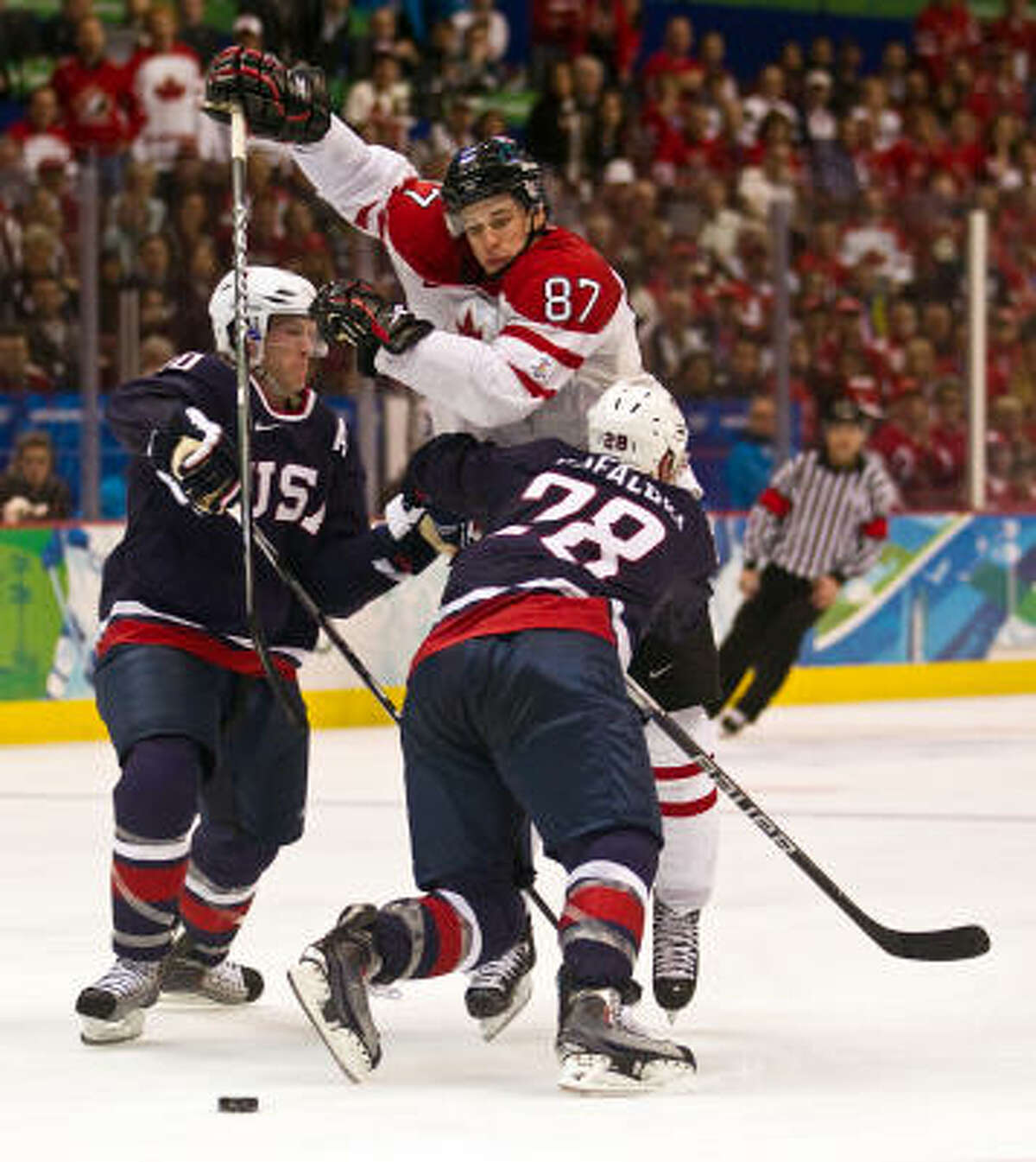 USA's Ryan Suter and Brian Rafalski try to hold up Canada's Sidney Crosby as Crosby brings the puck into the USA zone just before scoring the game-winner during the overtime period in the men's ice hockey gold medal game.