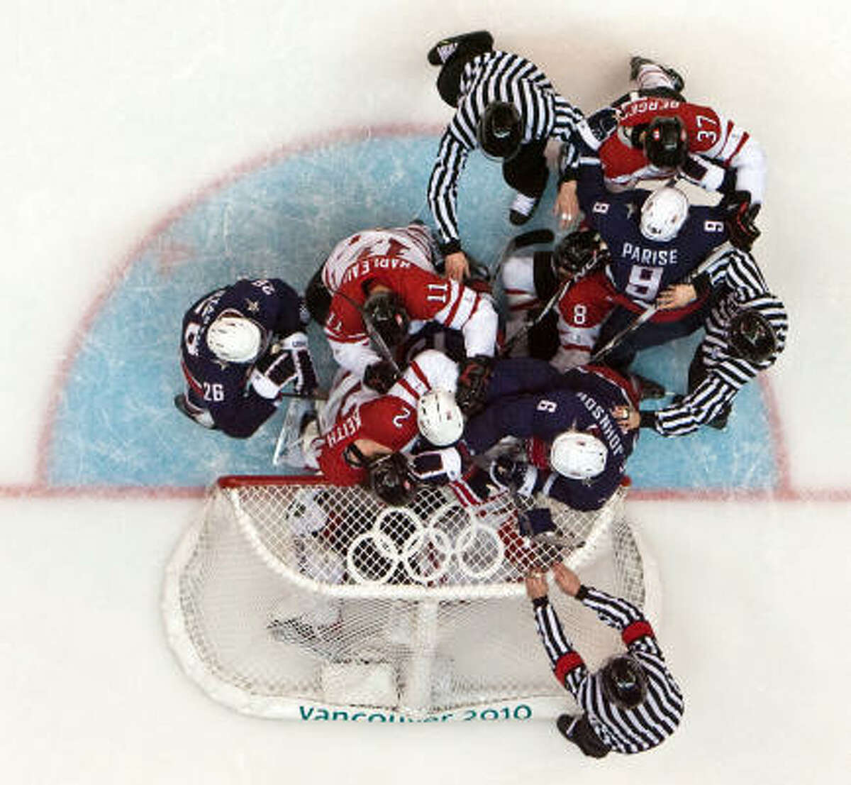Officials rush in to break up a shoving match in front of Canada goalie Roberto Luongo during the men's ice hockey gold medal game.