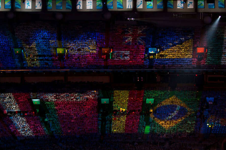 The flags of nations are projected on the audience during the Closing Ceremony. Photo: Smiley N. Pool, Chronicle Olympic Bureau