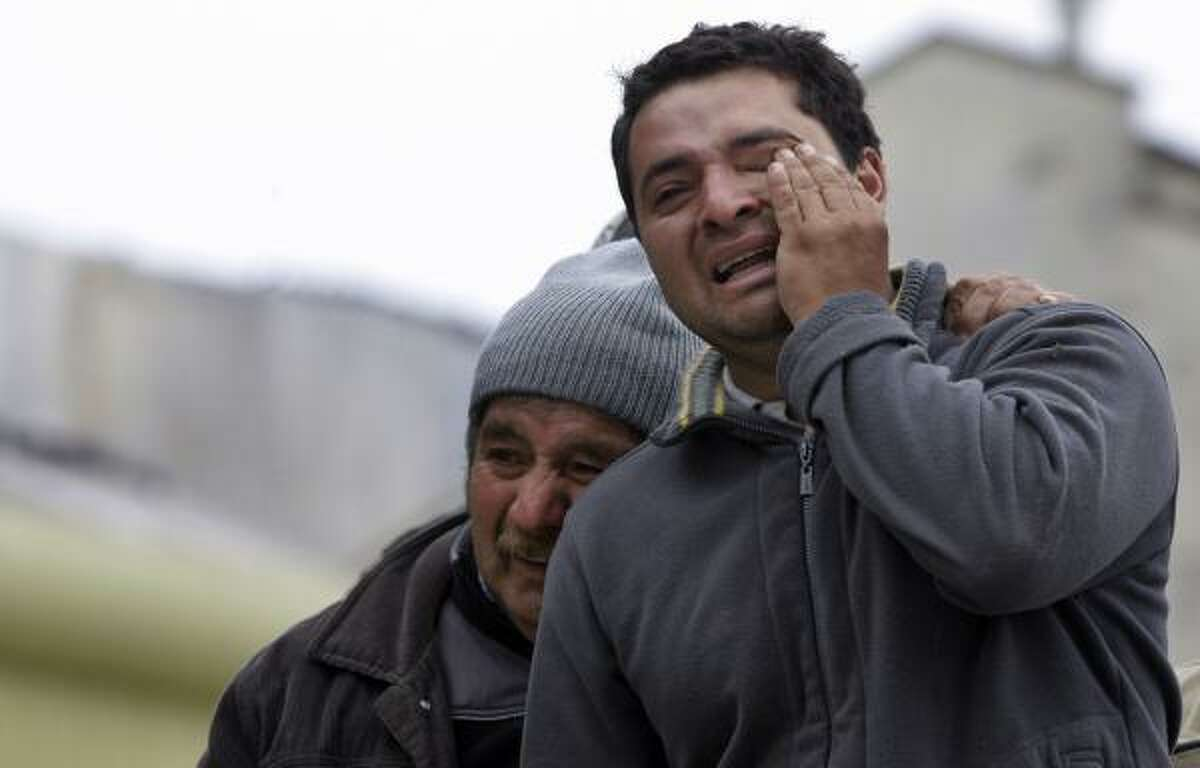 Relatives of victims grieve outside a destroyed building in the hard-hit city of Concepcion.