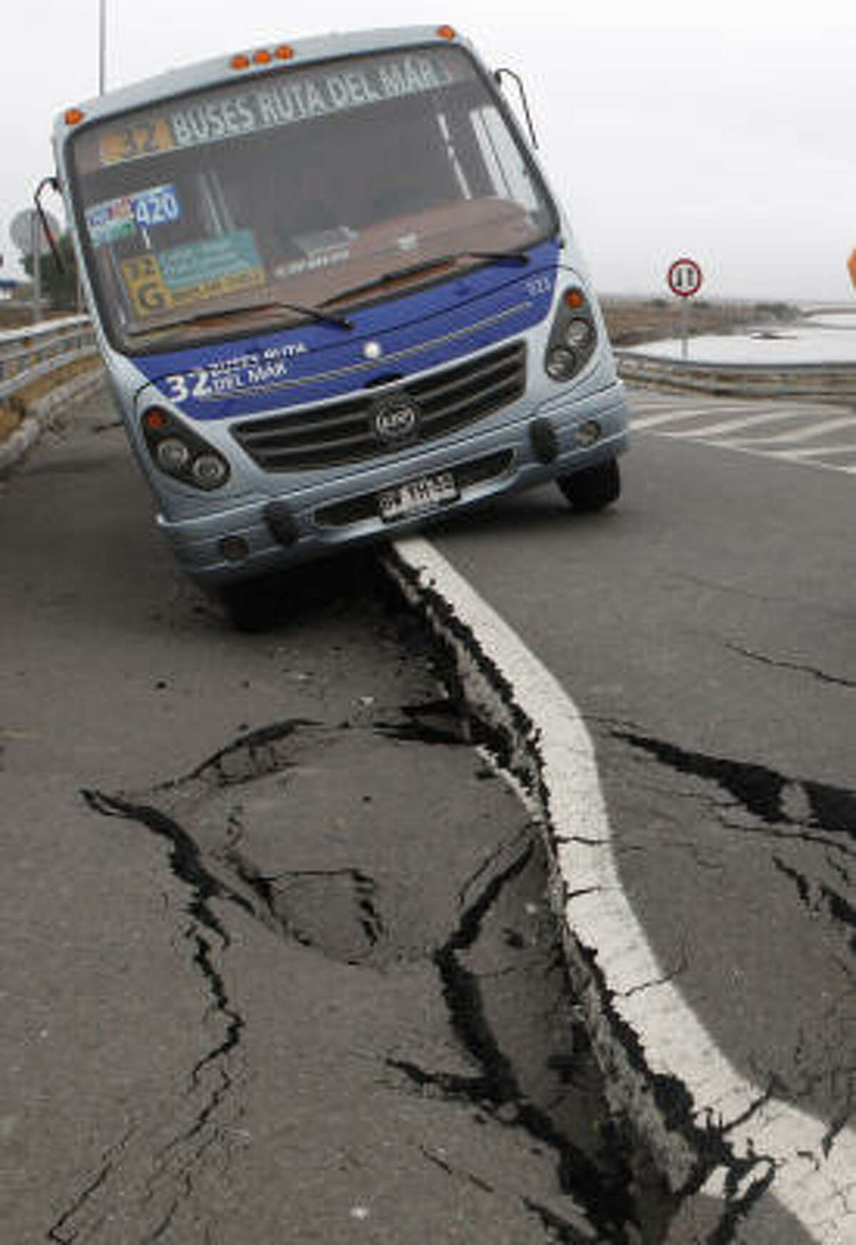 A parked bus leans on a destroyed road in Talcahuano, Chile.