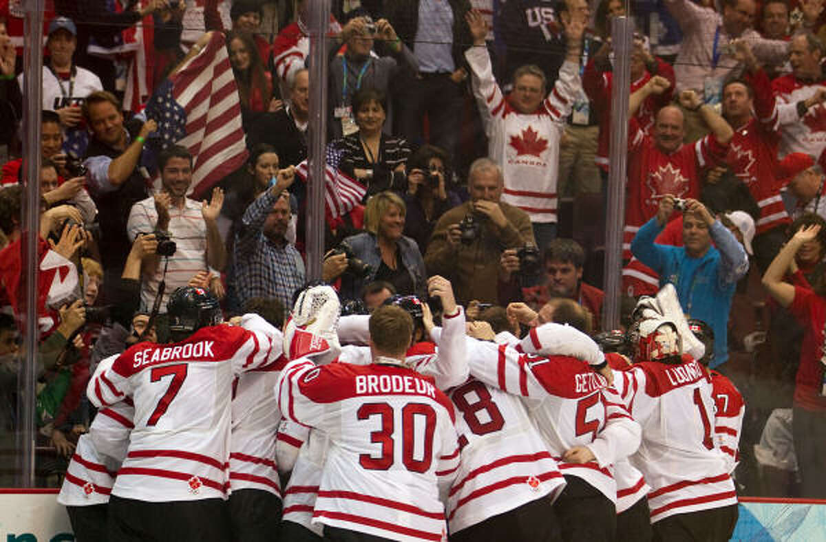 Team Canada celebrates after Sidney Crosby put the game-winner past Ryan Miller.