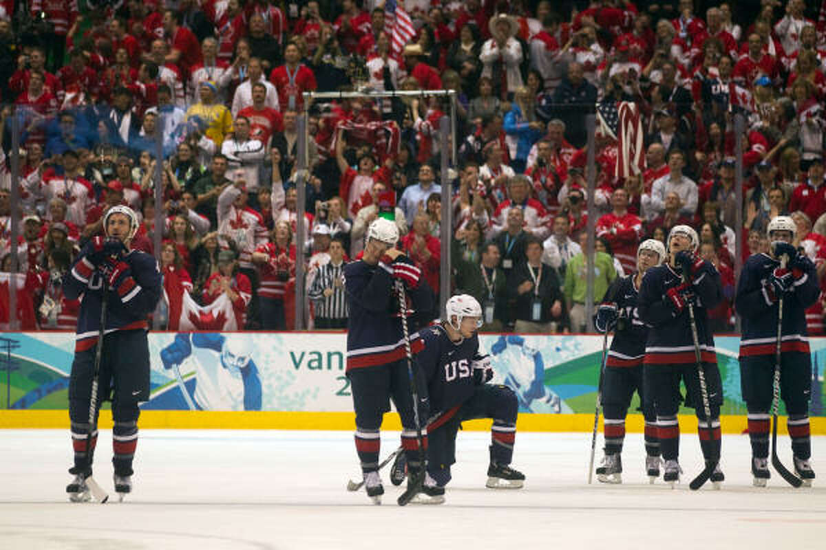 Team USA players stand by and watch as Canada players celebrate Sidney Crosby's game-winning goal.