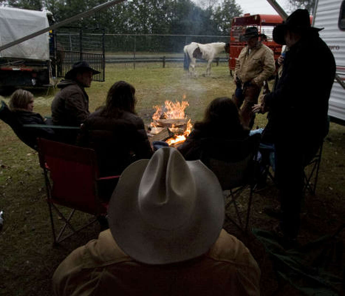Members of the Sam Houston Trail Ride gather around a fire at the groups overnight stop at Spring Creek Park Tuesday, Feb. 23, 2010, in Tomball.