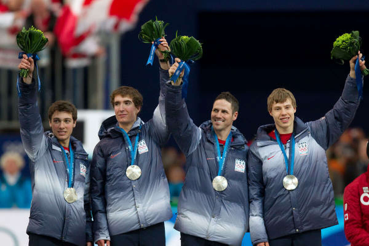 U.S. speedskaters, from left, Trevor Marsicano, Jonathan Kuck, Chad Hedrick and Brian Hansen wave from the awards stand.