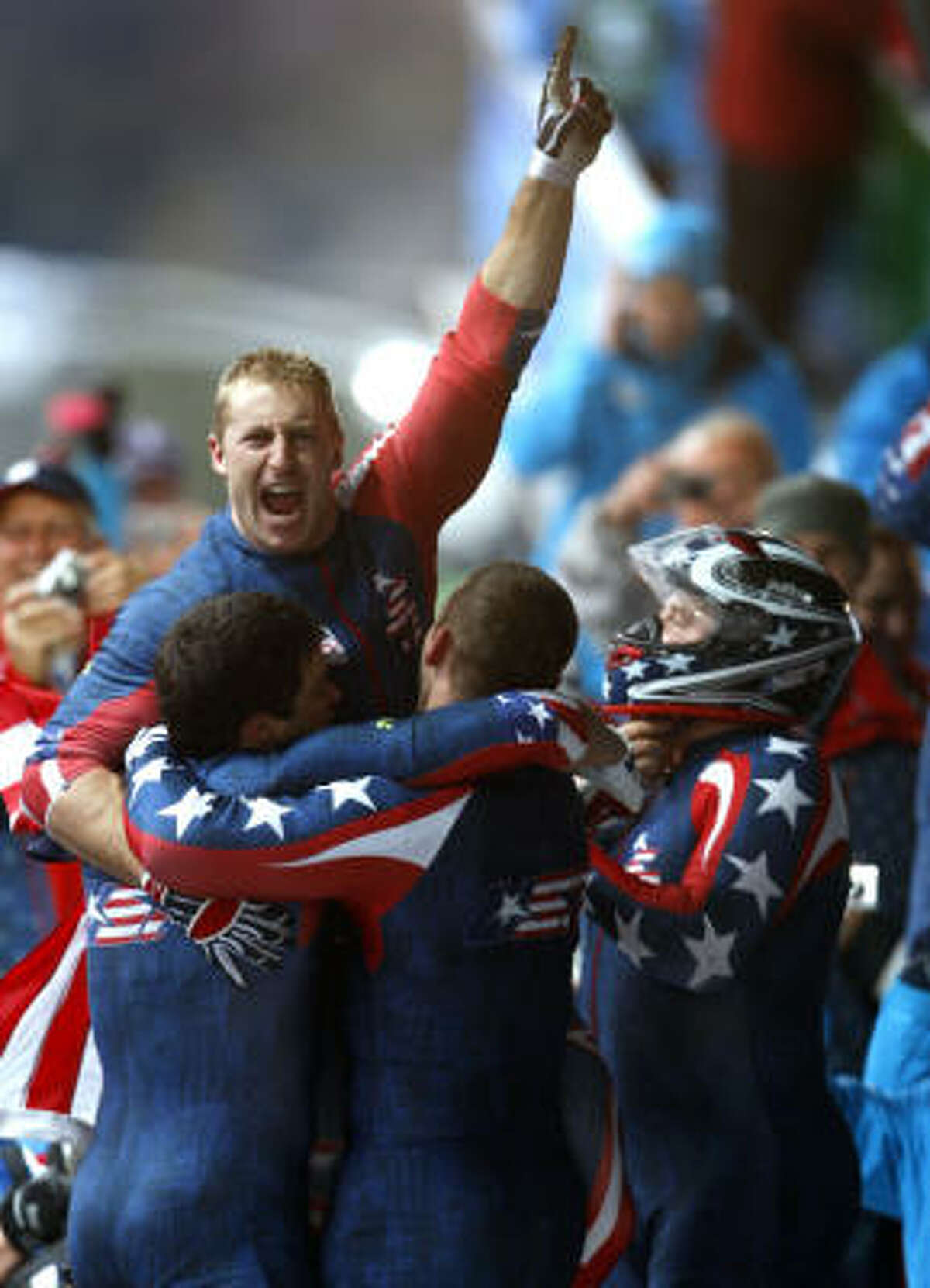 Curtis Tomasevicz and his USA 1 sled teammates celebrate their gold medal in Saturday's four-man bobsled competition.