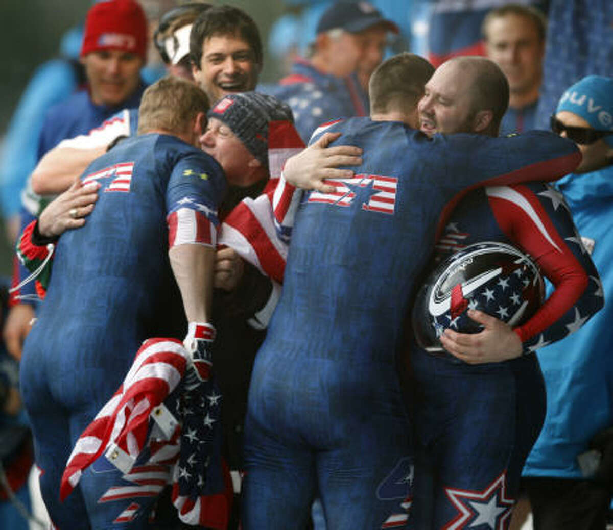 Steven Holcomb, right, and his teammates celebrate their gold medal win.