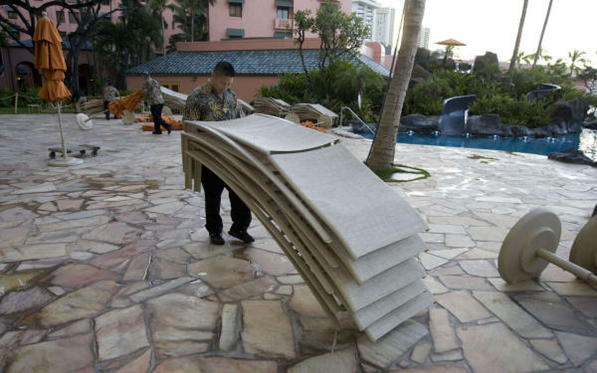 Aaron Okura, an employee of a hotel in the Waikiki area of Honolulu, helps move several lounge chairs from the swimming-pool area of the hotel Saturday, Feb. 27, 2010.