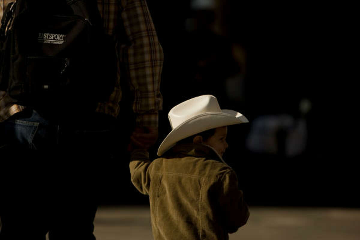 Omar Narraez, 2, of Houston walks with his father, Waldo, to watch the 72nd annual Rodeo Parade, Saturday, Feb. 27, 2010, in Houston.