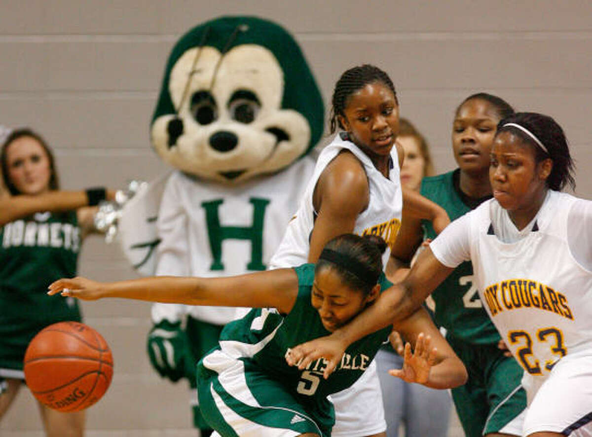 Huntsville guard Alexis Green, left, tries to wrangle the ball from La Marque's Precious Payne in the second quarter.