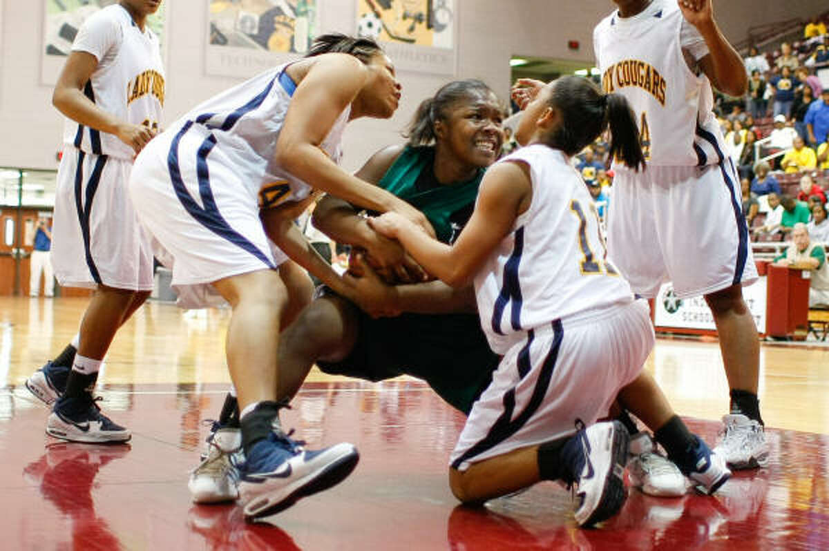 Huntsville's Shonecra James, center, is fouled by a host of La Marque players after grabbing a rebound in the second quarter.