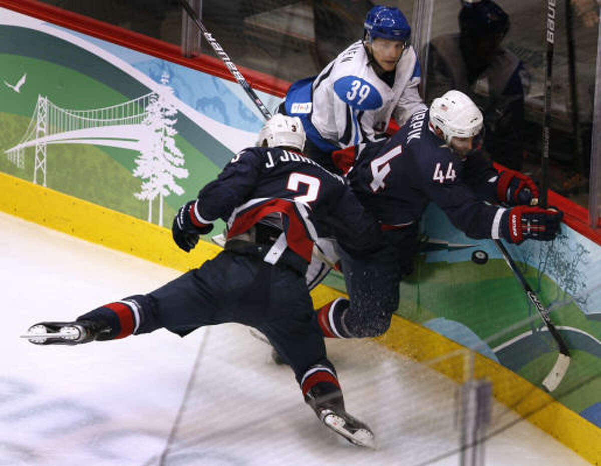 Jack Johnson and Brooks Orpik (44) of the United States tangle with Finland's Niko Kapanen in the third period of their semifinal hockey game.