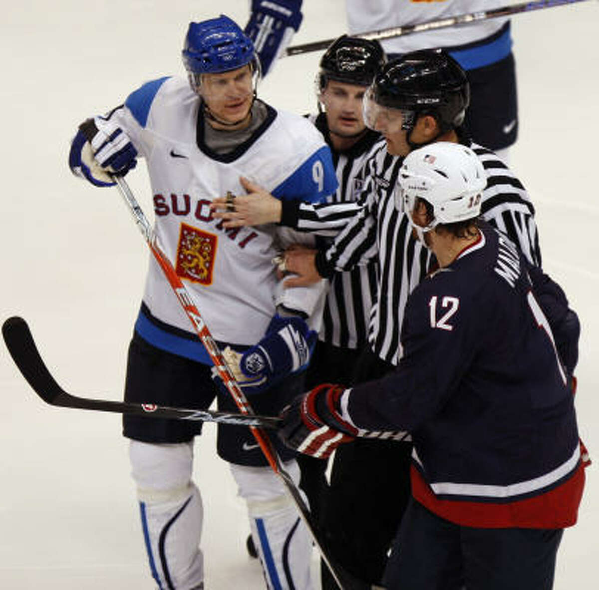 Linesmen separate FInland's Mikko Koivu and Ryan Malone of the United States after Malone's high sticking penalty in the third period.
