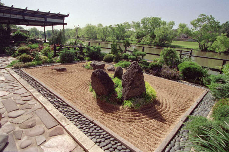 "In this Terry Vekris-designed Zen garden, a rectangular bed of raked gravel is edged in polished limestone and blue-black moonrock. The gravel, representing a body of water, is raked into calming straight lines and in concentric circles, representing rippling movement around an ""island"" of low-growing juniper and three boulders. The cool, smooth moonstones flow around the perimeter like a river. Photo: John Everett, For The Chronicle"