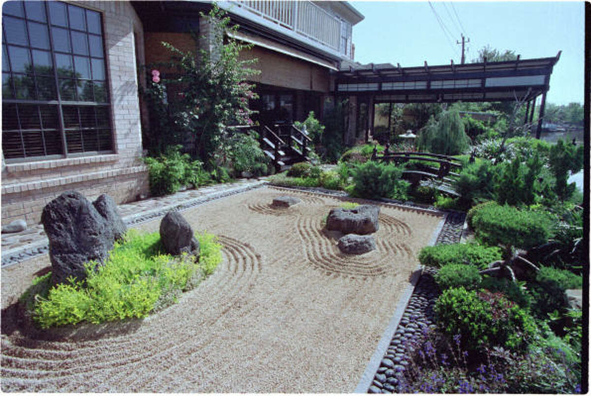 "In this Terry Vekris-designed Zen garden, a rectangular bed of raked gravel is edged in polished limestone and blue-black moonrock. The gravel, representing a body of water, is raked into calming straight lines and in concentric circles, representing rippling movement around an ""island"" of low-growing juniper and three boulders. The cool, smooth moonstones flow around the perimeter like a river."