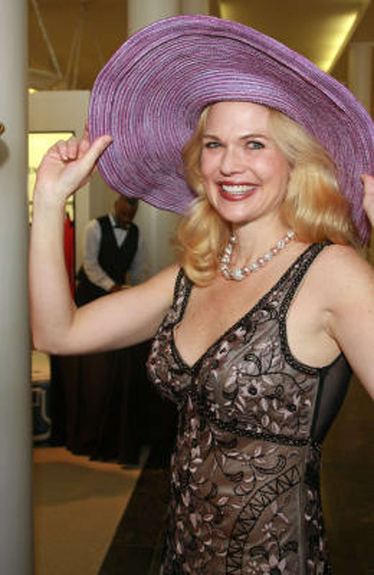 Amy Pierce tries on a hat at the third annual TUTS at Tootsies Style Show benefiting Theatre Under The Stars' education and outreach programs.