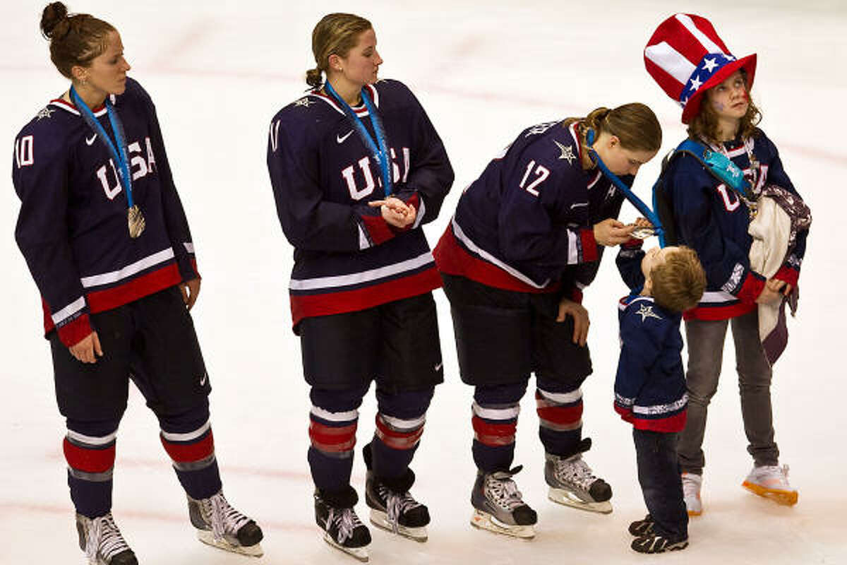 USA's Jenny Potter shows her silver medal to her son Cullen after the USA lost to Canada in the women's gold medal hockey game at the 2010 Winter Olympics in Vancouver.